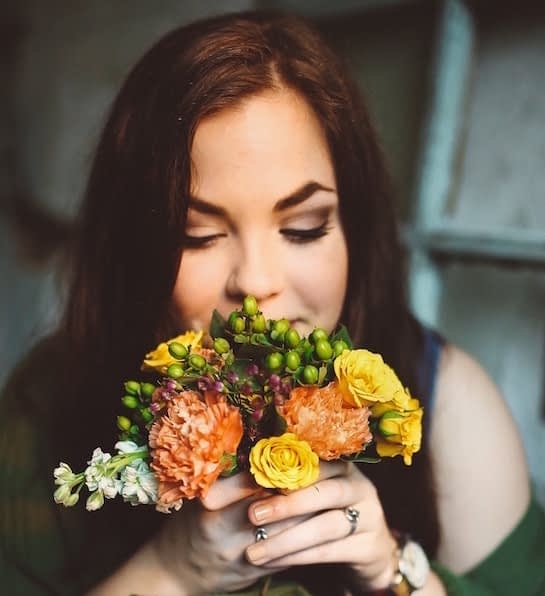 Young woman smelling bouquet flowers - Photo by Danielle Marroquin on Unsplash